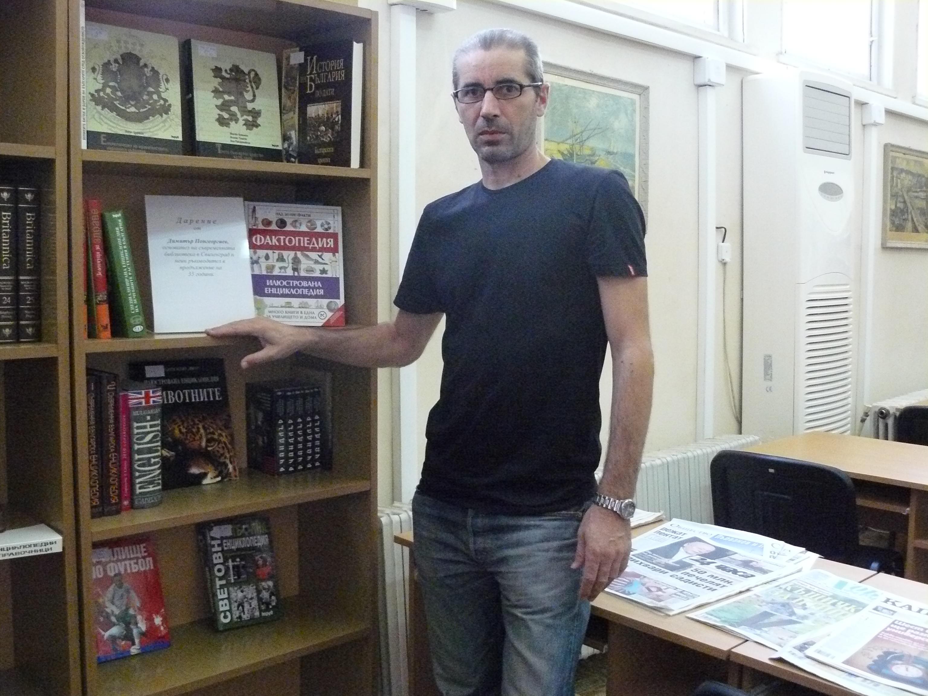Иван Чончев от библиотеката показва книгите, дарени от Димитър Попгеоргиев
